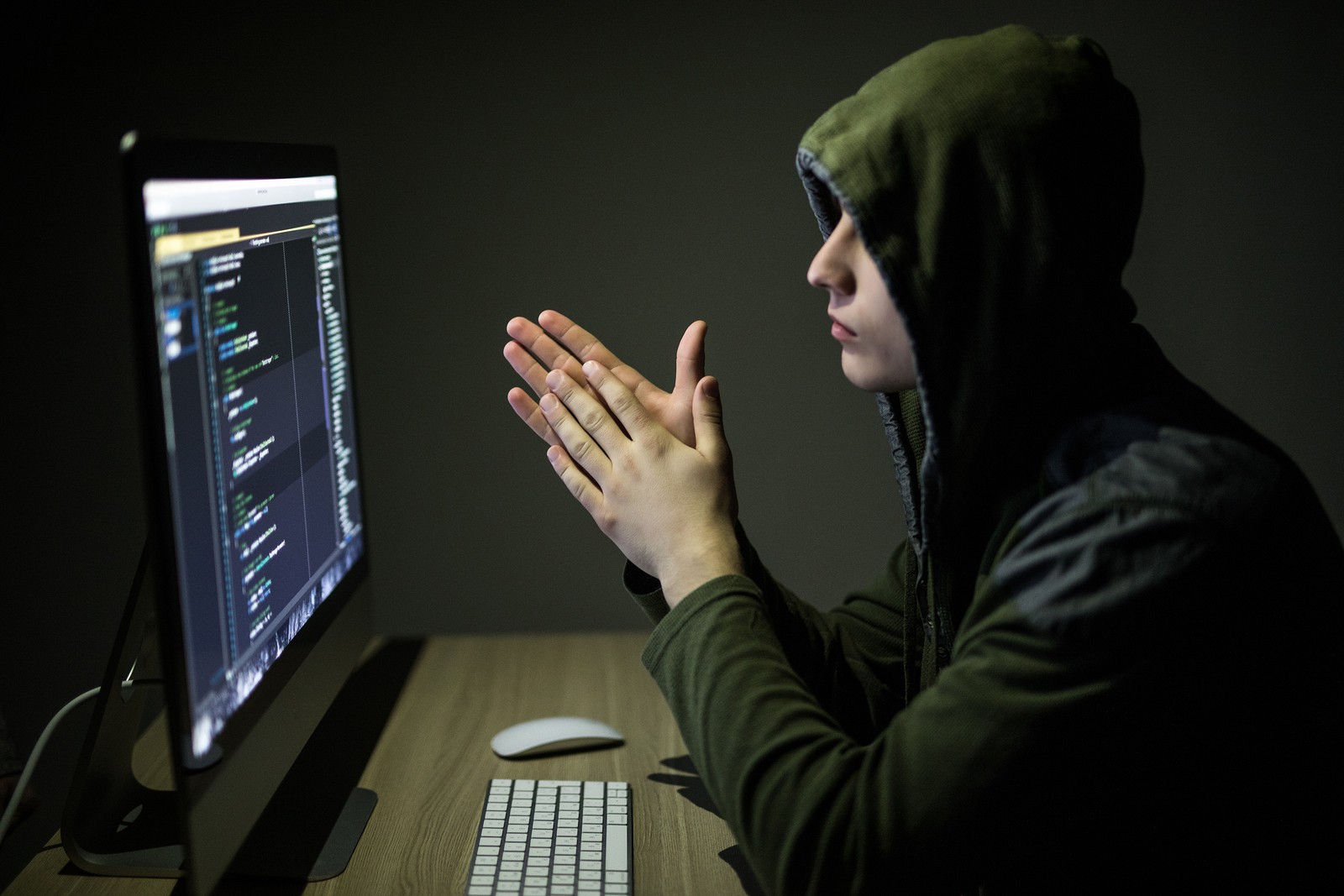 Hacker in glasses breaking code. Criminal hacker penetrating network system from his dark hacker room.